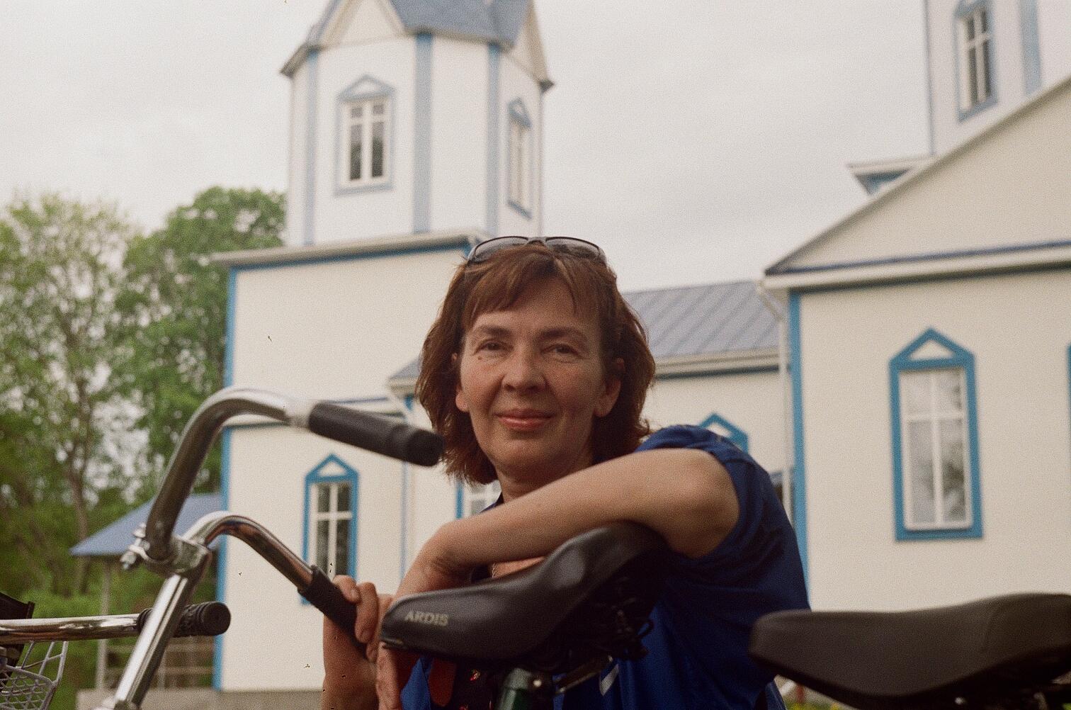 Анна Носова купным планом на фоне деревенской церкви