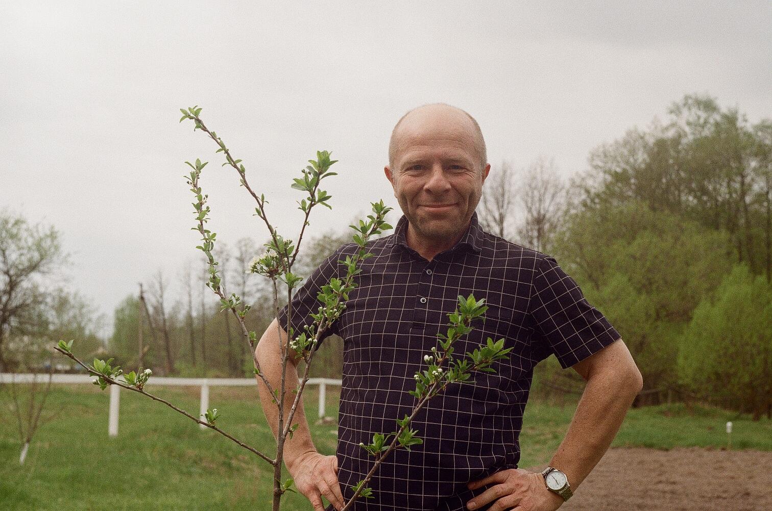 Юрий Павленко на даче на фоне саженца сливы